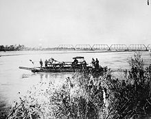Ferry on the Salt River carrying a horse and buggy. Railroad bridge seen in the background.