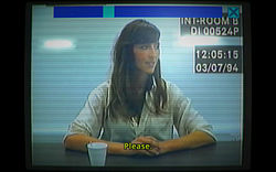 "Old computer footage of a 37-year-old woman in a white shirt with long brown hair, sitting at a police interview desk. She is holding her hands together in front of her, and is looking to the right of the camera. There is a subtitle that reads ""Please."" At the top of the screen is a scroll bar, positioned at one-third."