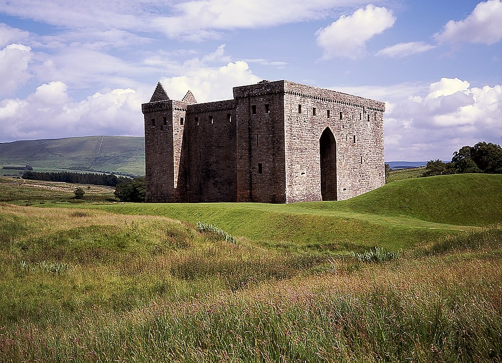 Hermitage Castle with green hills and trees surrounding it