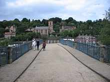 A view looking North along the roadway across the bridge, the curve  of its arch obscuring much of the town of Ironbridge behind. The town rises up the steep gorge side beyond with the Tontine Hotel and the Church of St Luke directly ahead.