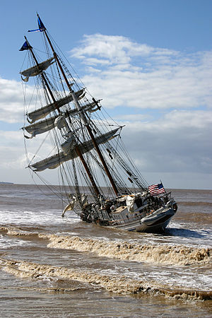 A sailing ship aground on a beach