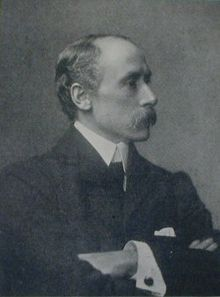 Black-and-white photographic profile portrait of a man in his forties, with a strong nose, moustache, receding hair, in a suit with his arms folded.