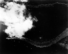 A distant overhead view of a patch of ocean; towards the left, partially obscured by a patch of cloud, is a large warship. The ship's wake trails out in a zig zag pattern behind her.