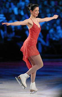 A female figure skater wearing a red dress, in profile as she lands a jump, extending her arms away from her perpendicular to the ice sheet for balance