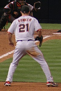 A man in a baseball uniform with his back to the camera