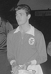 Black-and-white photo of a man donning an association football kit and holding a banner.