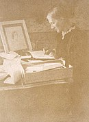 Julia writing letters at her desk in the drawing room of Talland House in 1892. On the desk is a drawing of her mother by Watts