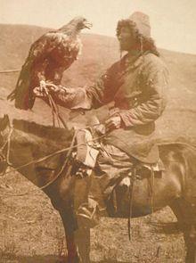 Photographie sépia d'un chasseur à cheval tenant un aigle.