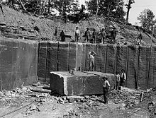 Workers standing in a quarry with a large stone block.