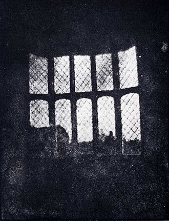 Lacock Abbey - A latticed window in Lacock Abbey, photographed by William Fox Talbot in 1835. Shown here in positive form, this may be the oldest extant photographic negative made in a camera.