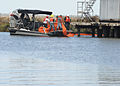 Louisiana contract workers place a containment boom around an oil storage tank in North Barataria Bay, La., near Myrtle Grove Sept 120902-G-TM873-710.jpg