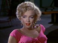 Monroe w Niagara.  Zbliżenie na jej twarz i ramiona;  ma na sobie złote kolczyki koła i szokującą różową górę
