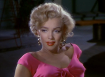 Monroe in Niagara. A close-up of her face and shoulders; she is wearing gold hoop earrings and a shocking pink top