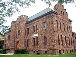 "A large brown stone building with castle-like towers and a pointed roof with step-like features on the end. Hanging from its right side is a banner that says ""Lake Plains YMCA"""