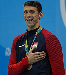 Michael Phelps with a gold medal hung around his neck on a red ribbon