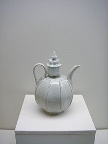 A white teapot with an almost perfectly spherical body and a large, cylindrical cap in the center which is topped with a small crown shaped embellishment. Several vertical lines are glazed into the body of the pot.