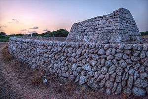 Naveta d'Es Tudons - The edifice at dawn, behind its modern wall