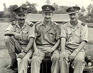 Three men in light-coloured uniforms with peaked caps seated on a jeep bonnet