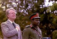Carter standing alongside Olusegun Obasanjo outside.
