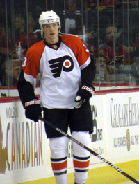 An ice hockey player is stood up straight by the edge of the rink. He is wearing a white uniform with orange shoulders and a stylised 'P' on his chest.