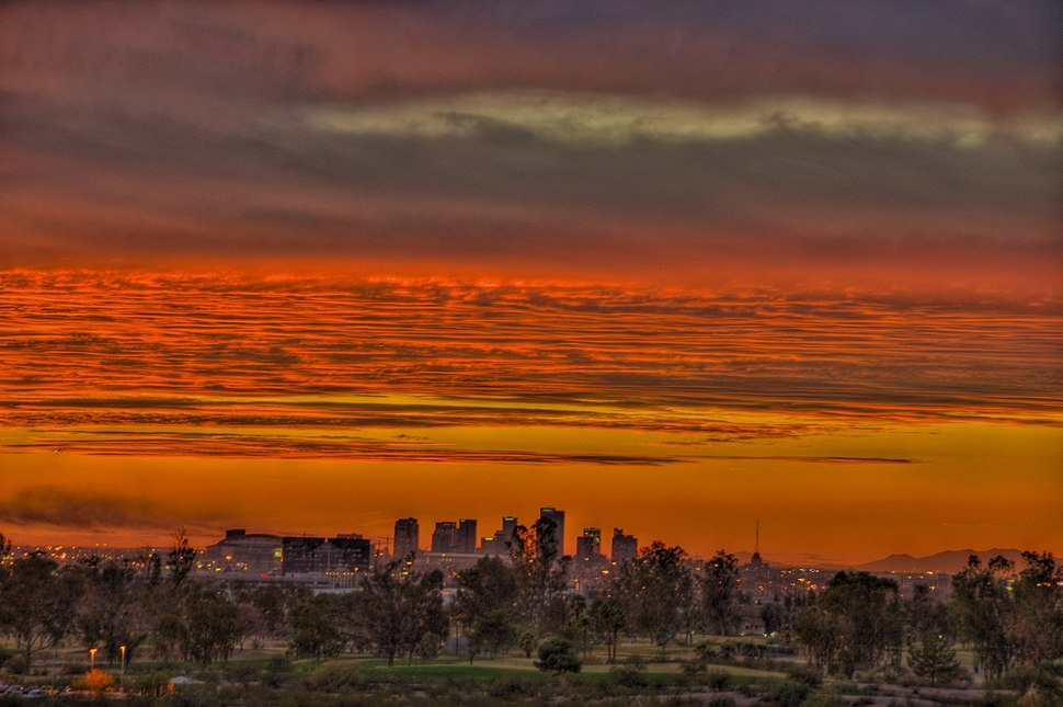 a photo of the reds and oranges of a sunset over the skyline of Phoenix, as seen from Papago park.