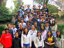 39 students stand on a staircase and face the camera. In the background is foliage.