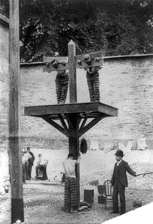 Pillory - Combined pillory and whipping post in New Castle County Jail, Delaware, 1907.  The pillory sits in an elevated position to increase its visibility, while the whipping post is at ground level to provide more room for the whipper.