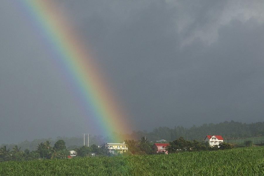 Rainbow over the house in the sugar cane fields. Location: Sainte-Marie, Réunion island, France.
