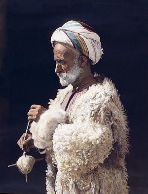 Hand spinning - A man from Ramallah spinning wool. Hand-tinted photograph from 1919, restored.