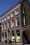 foto van Herenhuis met dwars schilddak met kroonlijst met triglyphen en klossen; hardstenen ingangspartij. Lange achtervleugel aan de Kuipersstraat, ten dele met getraliede spitsboogvensters