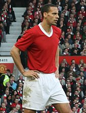 A mixed-race man with very short dark hair standing with his hands on his hips. He is wearing a red football shirt with a white V-neck and white shorts.
