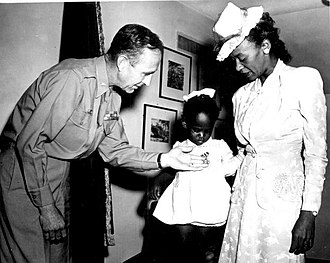 Robert Nicholas Young - BG Young as commander of the Military District of Washington with Melba Rose, age 2, daughter of Mrs. Rosie L. Madison, as they view the Silver Star awarded to her father 1LT John W. Madison, who was killed in action in Italy.