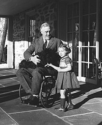 Roosevelt in a wheelchair on a patio, with a black dog on his lap, smiling, looks down at a young girl standing at his left side