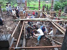 Dozens of men from an Indonesian village work on the foundation of a new building.