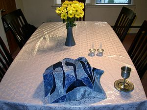 Challah cover -  A challah cover on a table set for Shabbat