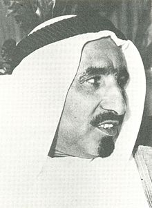 Black-and-white right-facing profile portrait of a man wearing a Van dyke beard and a keffiyeh.
