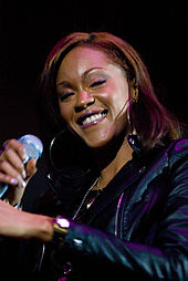 A picture of a woman wearing a black jacket and holding a microphone