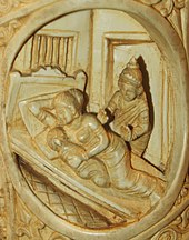 Ivory tusk showing a woman and a child sleeping on a bed, and a man standing besides the bed.