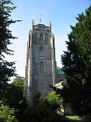 Square stone tower partially obscured by trees.
