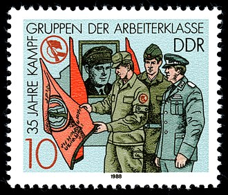 Combat Groups of the Working Class - Postage stamp in honor of the 35th anniversary of the KdA depicting Kampfern looking at the KdA flag.