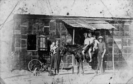StateLibQld 1 175087 Family in front of house made of kerosene tins at Wakerley, Brisbane, 1927.jpg