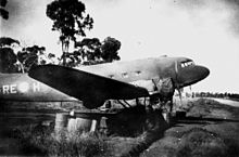 Twin-engined transport plane parked on a field near a fence