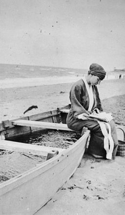 StateLibQld 1 66407 Woman sitting on a beached boat reading a book, ca. 1925