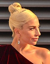 Lady Gaga with her hair in a bun atop her head, looks to the left.