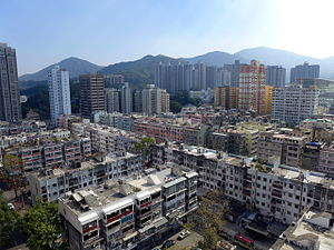 Tai Po - Tai Po Town. Older low-level buildings in the foreground contrast with high-rise commercial buildings in the distance
