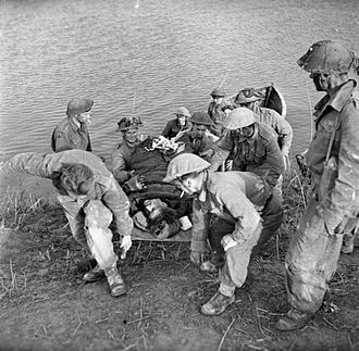 London Irish Rifles - A casualty is brought back across the River Reno during operations by 'C' Company of the 1st Battalion, London Irish Rifles to establish a bridgehead across the river, 6 April 1945.