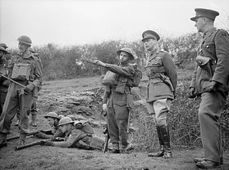 50th (Northumbrian) Infantry Division - King George VI watches troops taking part in manoeuvres during a visit to the 50th Division in Southern Command, 2 April 1941.