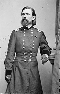 A man in his late thirties with black hair, a mustache, and a long, black beard. He is wearing a long military coat and gloves and is facing right.