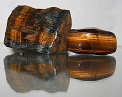 A photograph showing a polished reddish brown stone which is bisected by a band containing golden fibers