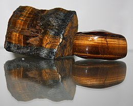 A polished reddish brown stone which is bisected by a band containing golden fibers